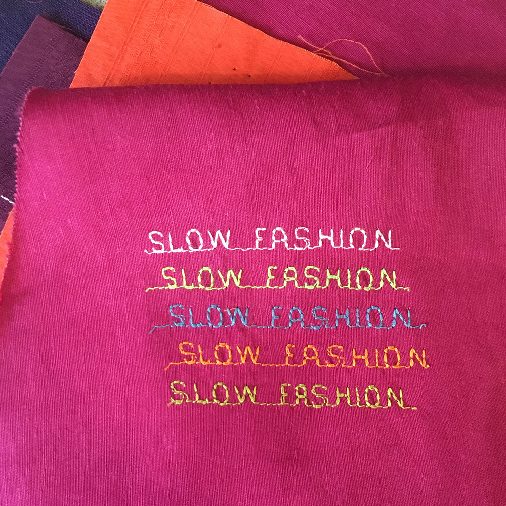 SLOW FASHION SLOW FASHION SLOW FASHION SLOW FASHION SLOW FASHION stitched in square letters on fuchsia colored fabric with orange and purple fabric in the background.
